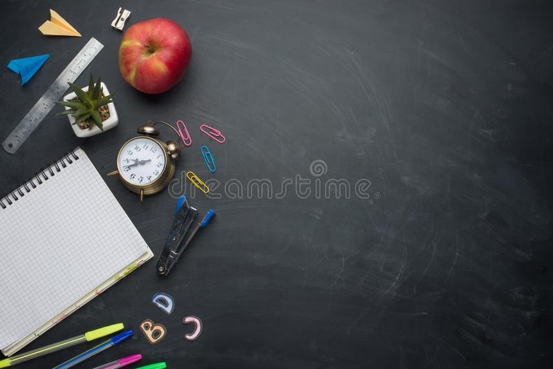 Banner concept Back to School Alarm clock, pencil Apple Notebook Stationery on blackboard background. Design Copy Space accessorie royalty free stock photos
