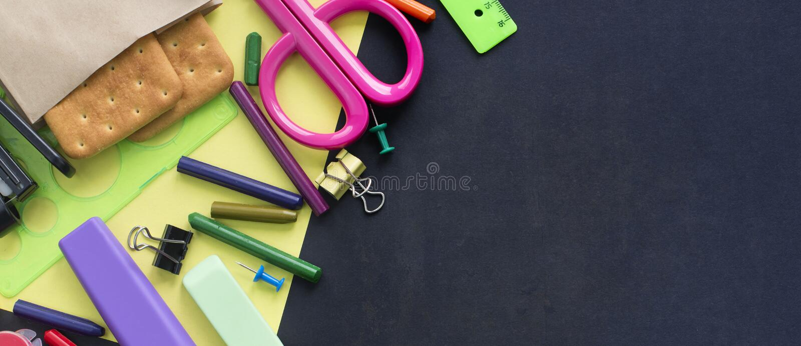 Banner Concept back to school watch chalk line cookies stationery on black background. Top view Flat lay stock photos