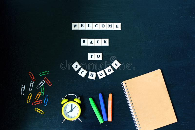 Banner Concept. Welcome back to School on black blackboard background. Top View. Flat Lay. Design. Copy Space Supplies. stock photos