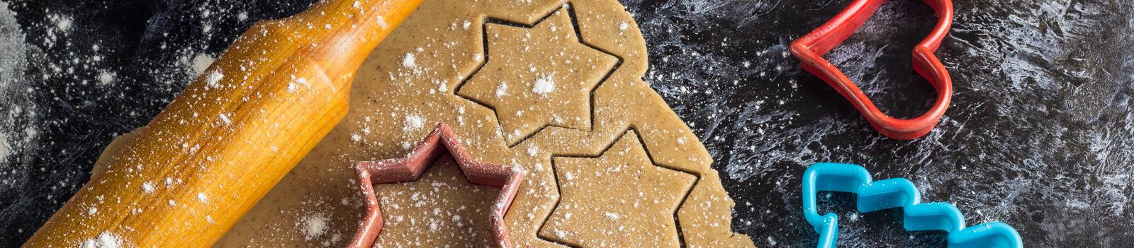Banner of Cooking Christmas gingerbread cookies with ingredients on a dark background royalty free stock image