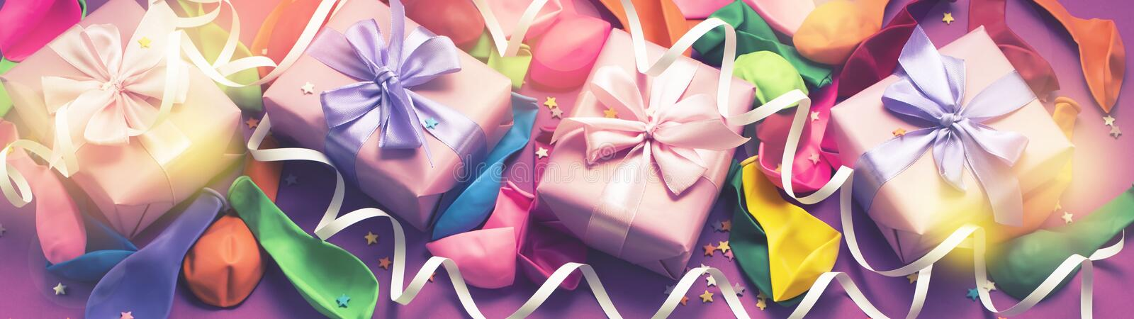 Banner Decorative box composition with gifts satin ribbon bow inflatable balls serpentine purple background A top view royalty free stock photo