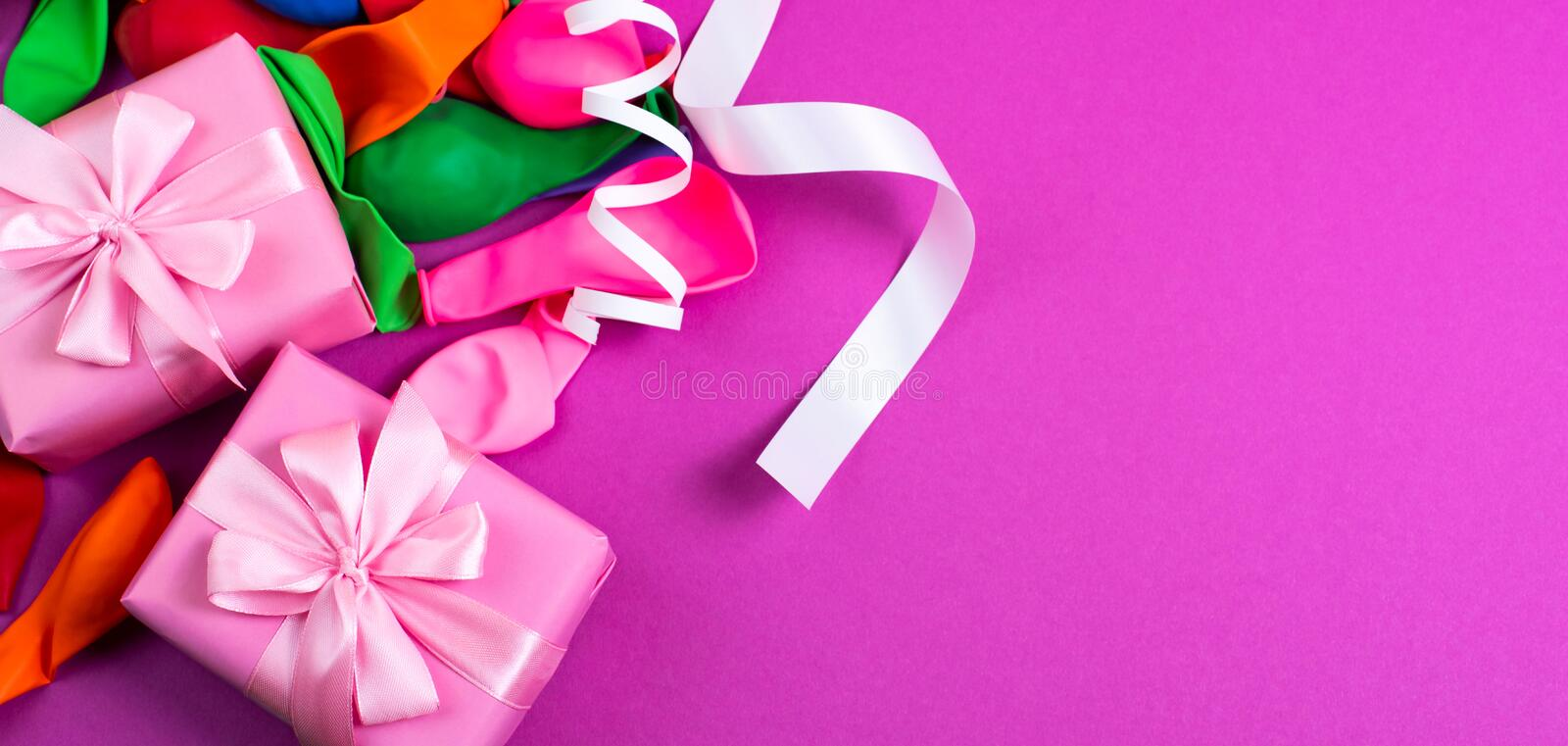 Banner Decorative box composition with gifts satin ribbon bow inflatable balls serpentine purple background A top view of Flat lay royalty free stock photography