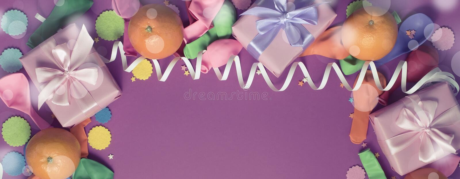 Banner Decorative composition Three boxes with gifts Satin ribbon Bow Oranges Confetti Serpentine birthday party. The view from the top royalty free stock image