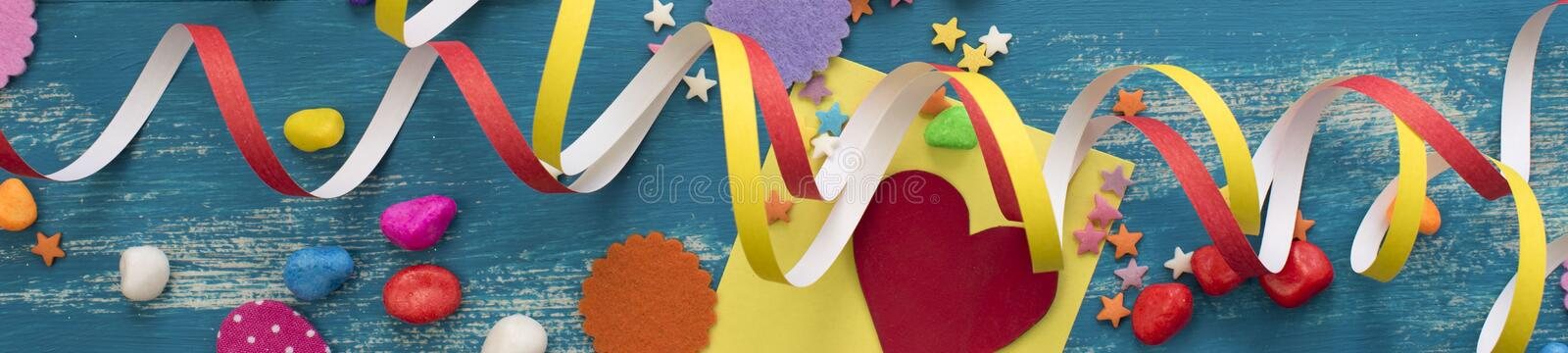 Banner Decorative holiday background with streamers confetti candy hearts decor. Blue shabby wooden top view background flat lay royalty free stock images