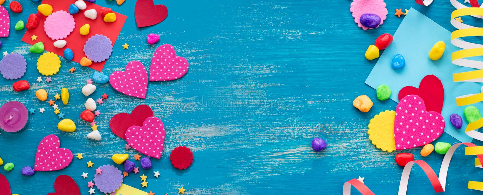 Banner Decorative holiday background with streamers confetti candy hearts decor. Blue shabby wooden top view background flat lay royalty free stock photos
