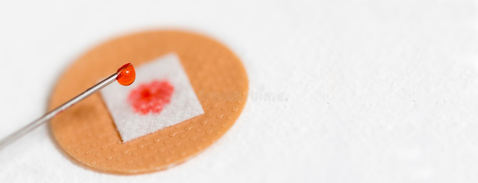 Drop of red liquid on an injection needle. Banner drop of red liquid on an injection needle and the blood on the plaster stock image