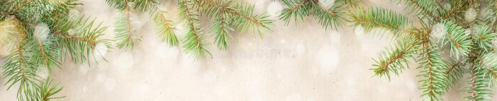 banner of Festive christmas border with fir branches and snowflakes with snow on rustic beige background royalty free stock images