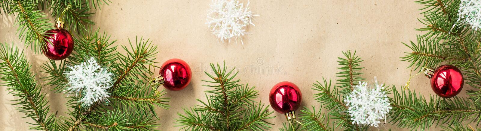 Banner of Festive christmas border with red balls on fir branches and snowflakes on rustic beige background royalty free stock photography