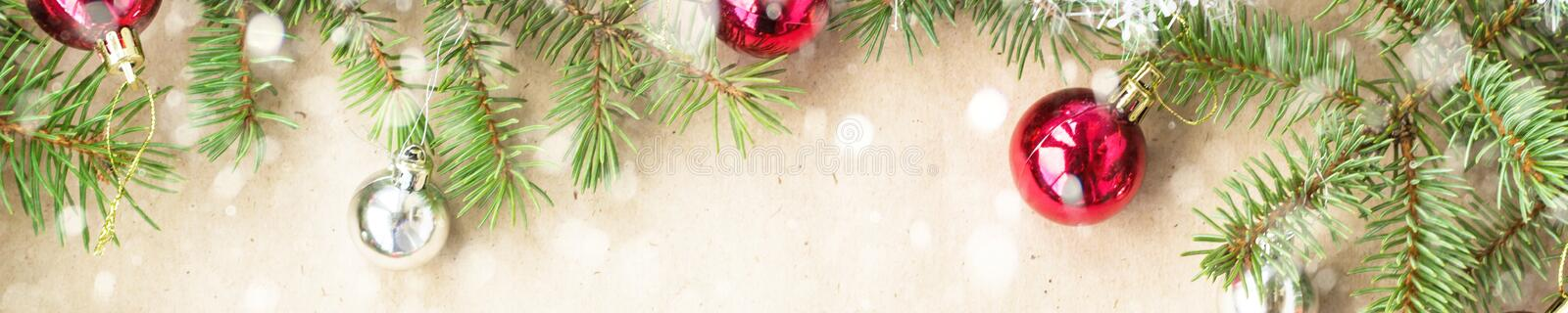 Banner of Festive christmas border with red balls on fir branches and snowflakes with snow on rustic beige background stock photography
