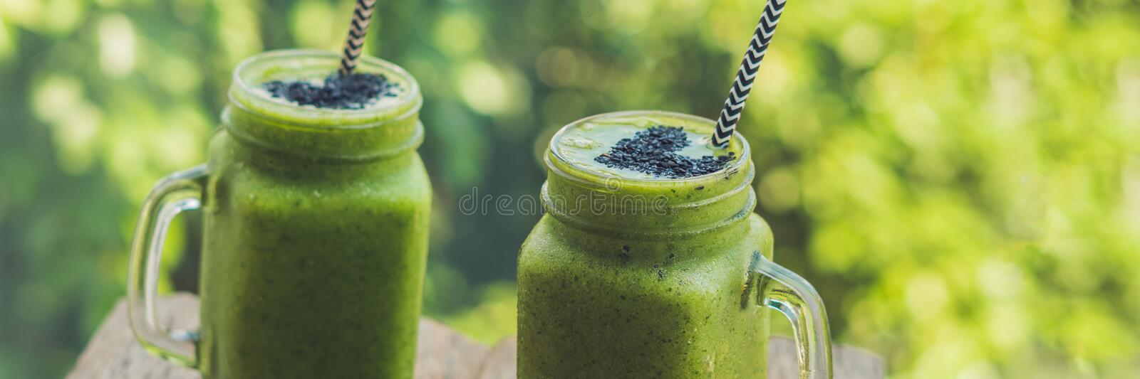 BANNER Fresh green smoothie with banana and spinach with heart of sesame seeds. Love for a healthy raw food concept Long Format. BANNER Fresh green smoothie with royalty free stock photography