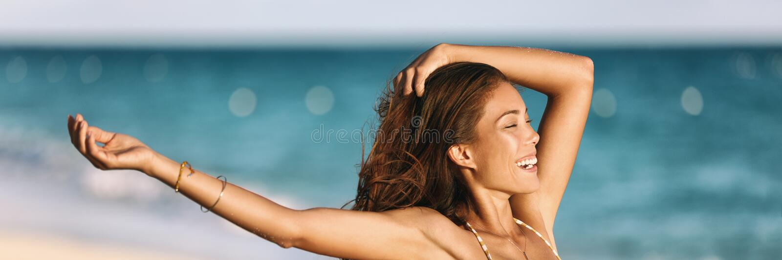 Banner happy woman carefree with arms up smiling laughing in ocean beach panoramic background on tropical Caribbean summer. Vacation panorama. Asian girl stock image