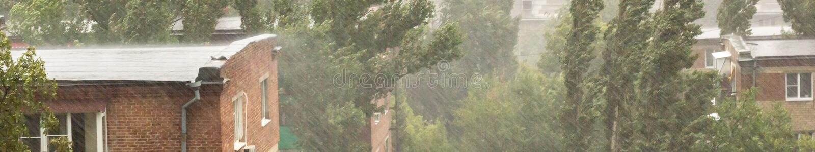 banner of Heavy rain, trees, wire and residential house in the village stock image