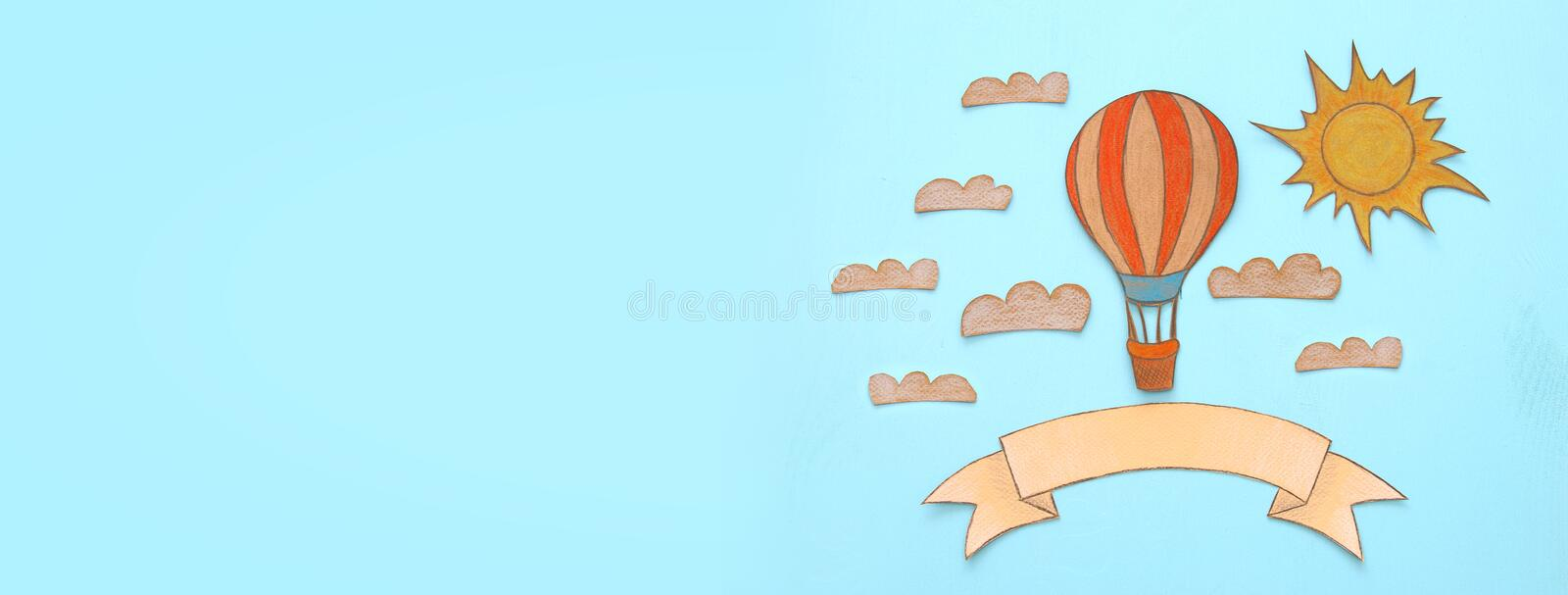 Banner of Hot air balloon, space elements shapes cut from paper and painted over wooden blue background. vector illustration