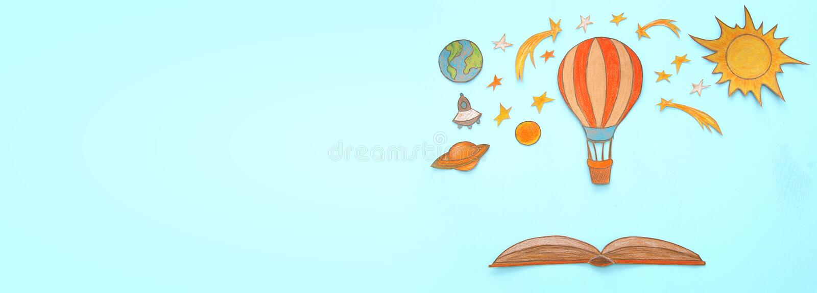 Banner of Hot air balloon, space elements shapes cut from paper and painted over wooden blue background. royalty free illustration