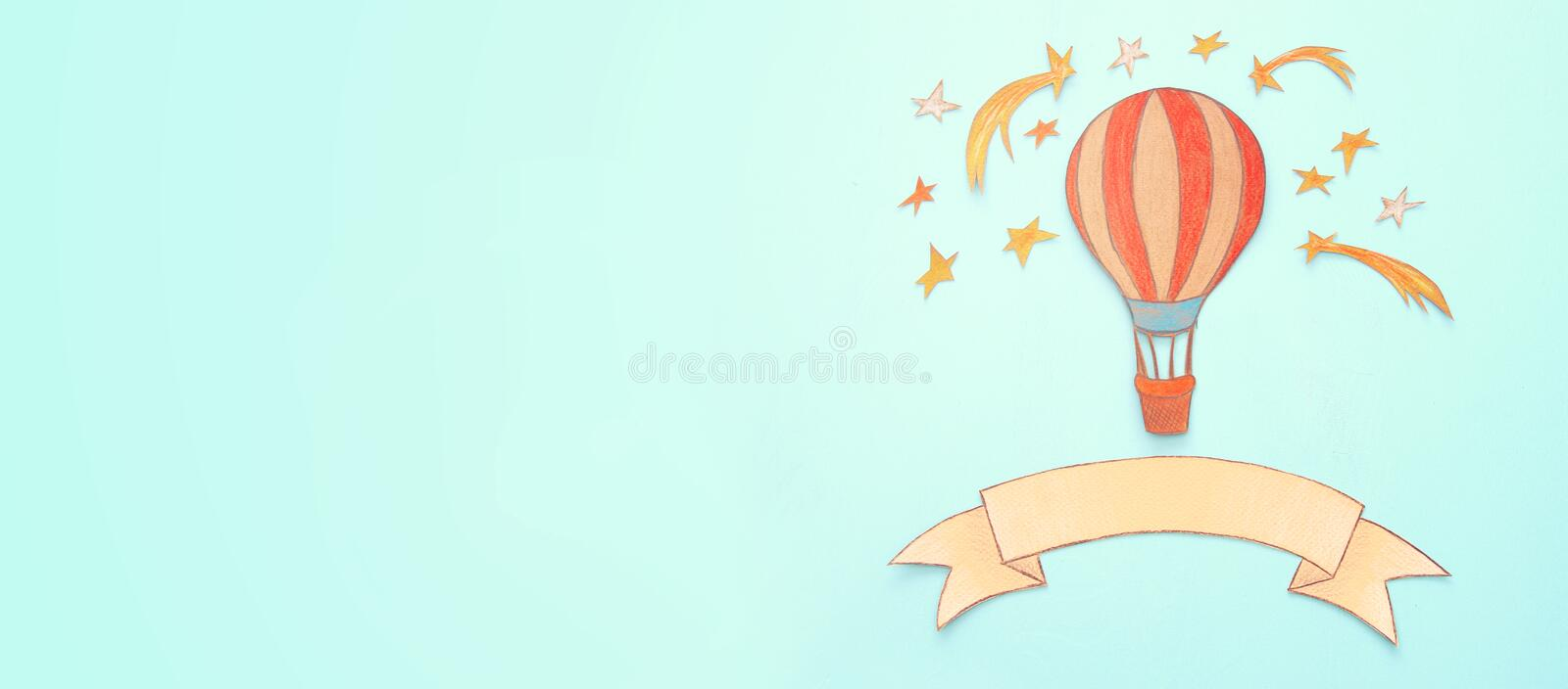 Banner of Hot air balloon, space elements shapes cut from paper and painted over wooden blue background. royalty free stock image
