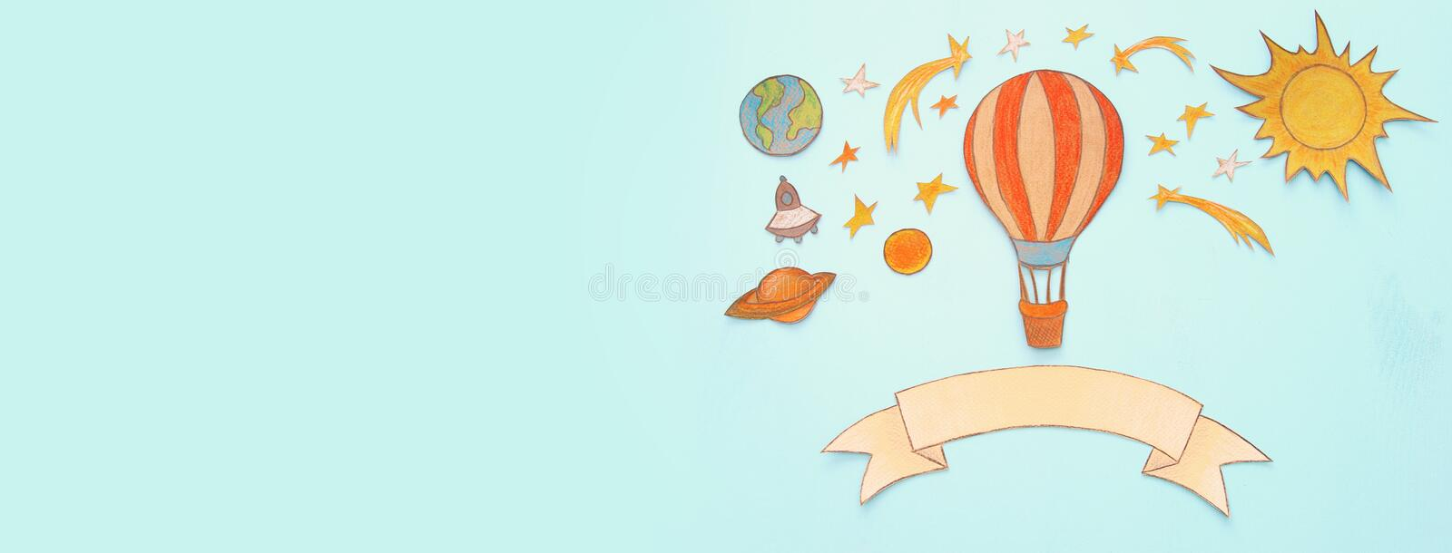 Banner of Hot air balloon, space elements shapes cut from paper and painted over wooden blue background. royalty free stock photography