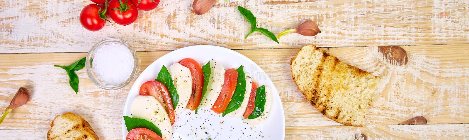 Banner with Italian caprese salad with sliced tomatoes, mozzarella cheese, basil, olive oil. On wooden background. Top view with space for your text stock images