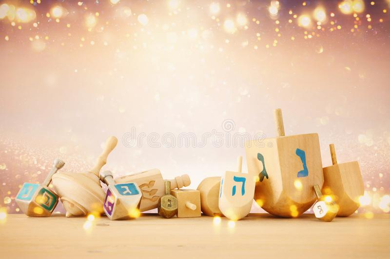 Banner of jewish holiday Hanukkah with wooden dreidels & x28;spinning top& x29; over glitter shiny background. royalty free illustration