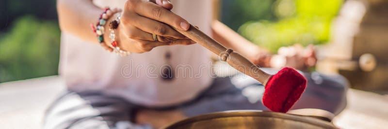 BANNER, LANGE het koper zingende kom van FORMAATnepal Boedha bij kuuroordsalon Jonge mooie vrouw die massagetherapie het zingen d stock fotografie