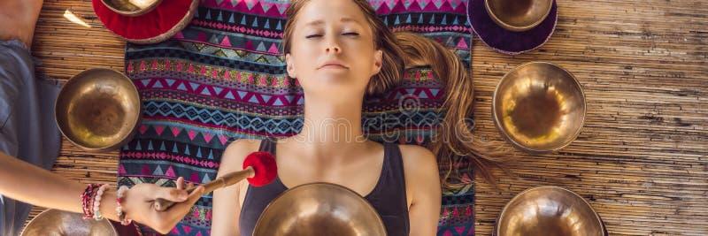 BANNER, LANGE het koper zingende kom van FORMAATnepal Boedha bij kuuroordsalon Jonge mooie vrouw die massagetherapie het zingen d royalty-vrije stock fotografie