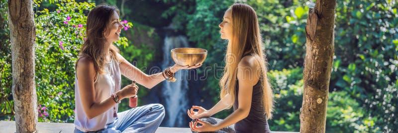 BANNER, LANGE het koper zingende kom van FORMAATnepal Boedha bij kuuroordsalon Jonge mooie vrouw die massagetherapie het zingen d stock foto's