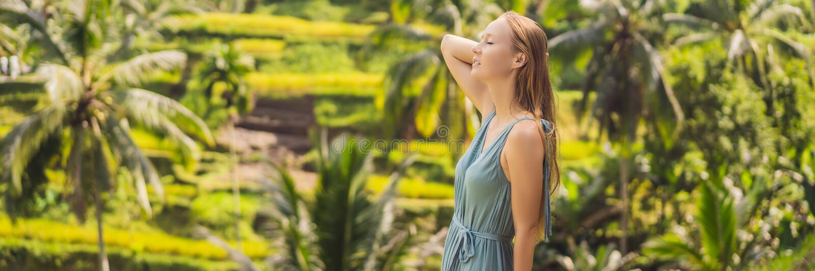 BANNER, LONG FORMAT Beautiful young woman walk at typical Asian hillside with rice farming, mountain shape green cascade royalty free stock photo