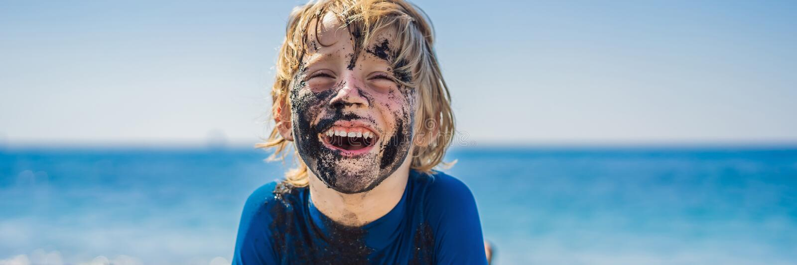 BANNER, LONG FORMAT Black Friday concept. Smiling boy with dirty Black face sitting and playing on black sand sea beach stock photography