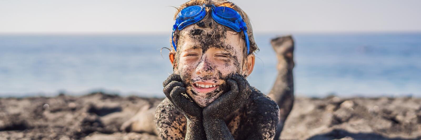 BANNER, LONG FORMAT Black Friday concept. Smiling boy with dirty Black face sitting and playing on black sand sea beach royalty free stock photography