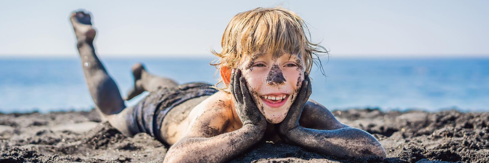 BANNER, LONG FORMAT Black Friday concept. Smiling boy with dirty Black face sitting and playing on black sand sea beach stock image