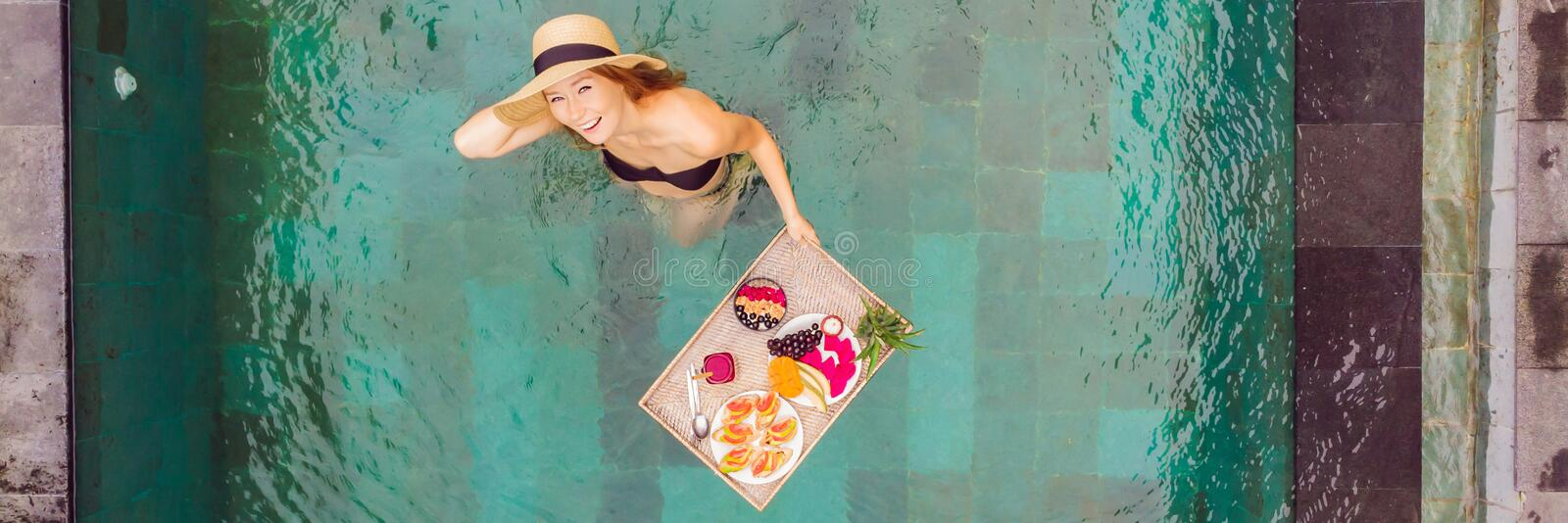 BANNER, LONG FORMAT Breakfast tray in swimming pool, floating breakfast in luxury hotel. Girl relaxing in the pool. Drinking smoothies and eating fruit plate royalty free stock photo