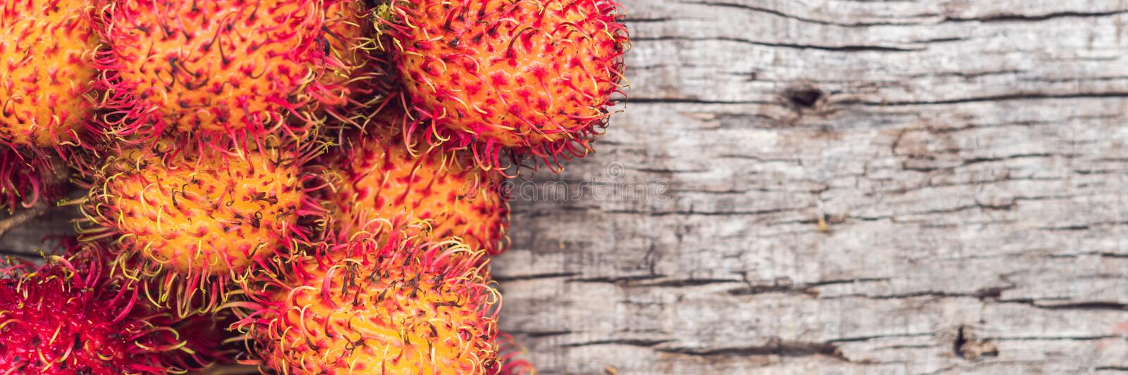 BANNER, Long Format Fresh rambutan fruit on wooden teble background, closeup, fruit in Thailand royalty free stock images