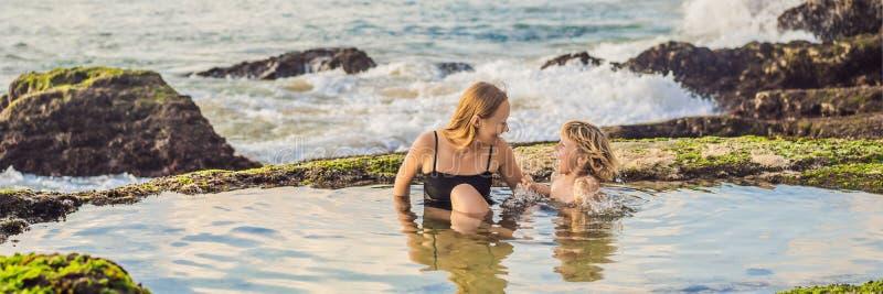 BANNER, LONG FORMAT Mère et fils touristes sur la plage de Pantai Tegal Wangi, dans un bain d'eau de mer, île de Bali photos stock