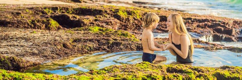 BANNER, LONG FORMAT Mère et fils touristes sur la plage de Pantai Tegal Wangi, dans un bain d'eau de mer, île de Bali photo stock