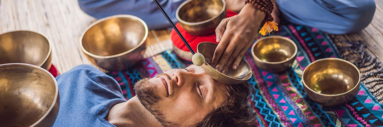 BANNER, LONG FORMAT Nepal Buddha copper singing bowl at spa salon. Young beautiful man doing massage therapy singing. BANNER, LONG FORMAT Nepal Buddha copper stock images