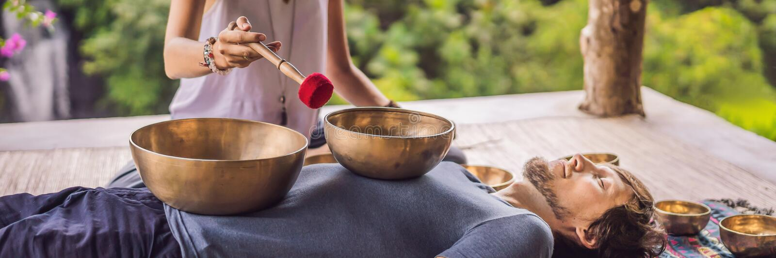 BANNER, LONG FORMAT Nepal Buddha copper singing bowl at spa salon. Young beautiful man doing massage therapy singing. BANNER, LONG FORMAT Nepal Buddha copper royalty free stock images