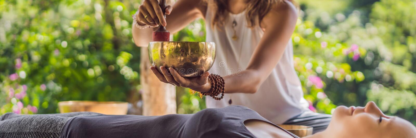 BANNER, LONG FORMAT Nepal Buddha copper singing bowl at spa salon. Young beautiful woman doing massage therapy singing. BANNER, LONG FORMAT Nepal Buddha copper royalty free stock photo
