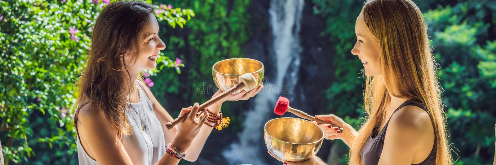 BANNER, LONG FORMAT Nepal Buddha copper singing bowl at spa salon. Young beautiful woman doing massage therapy singing. BANNER, LONG FORMAT Nepal Buddha copper royalty free stock image