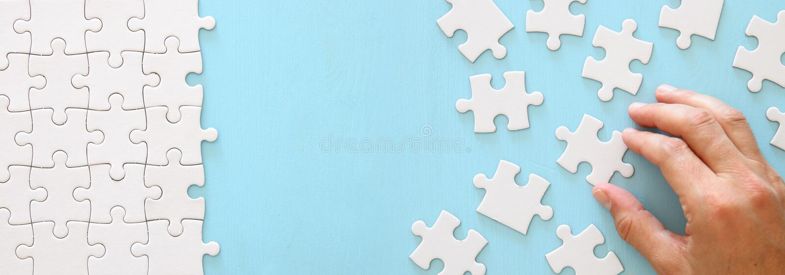 banner of male hand putting the last piece in the puzzle. stock photos