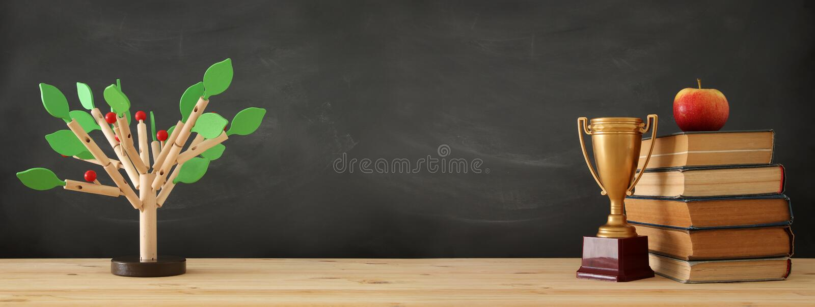 banner of open book, gold trophy and wooden tree puzzle over blackboard background. education and knowledge concept. stock photo