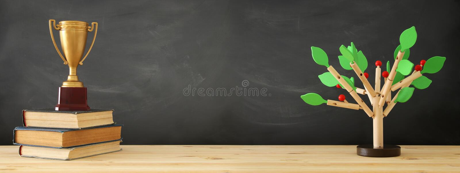banner of open book, gold trophy and wooden tree puzzle over blackboard background. education and knowledge concept. stock photos