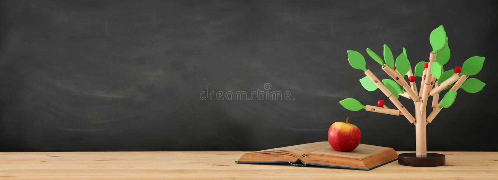 banner of open book and wooden tree puzzle over blackboard background. education and knowledge concept. royalty free stock photo
