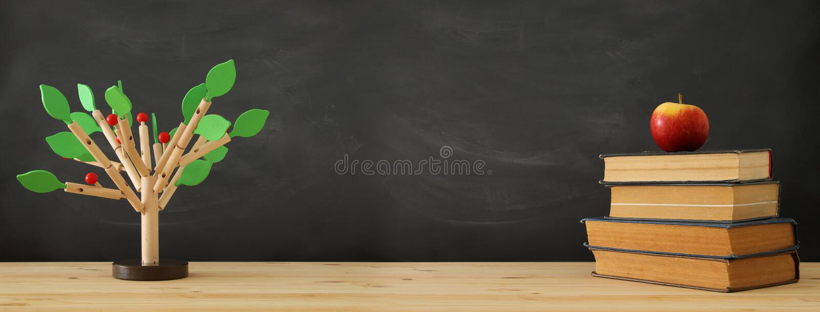 banner of open book and wooden tree puzzle over blackboard background. education and knowledge concept. stock image