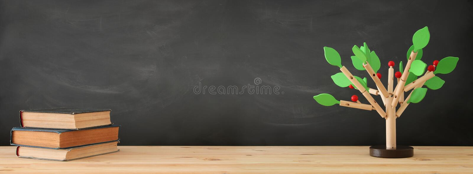 banner of open book and wooden tree puzzle over blackboard background. education and knowledge concept. royalty free stock image
