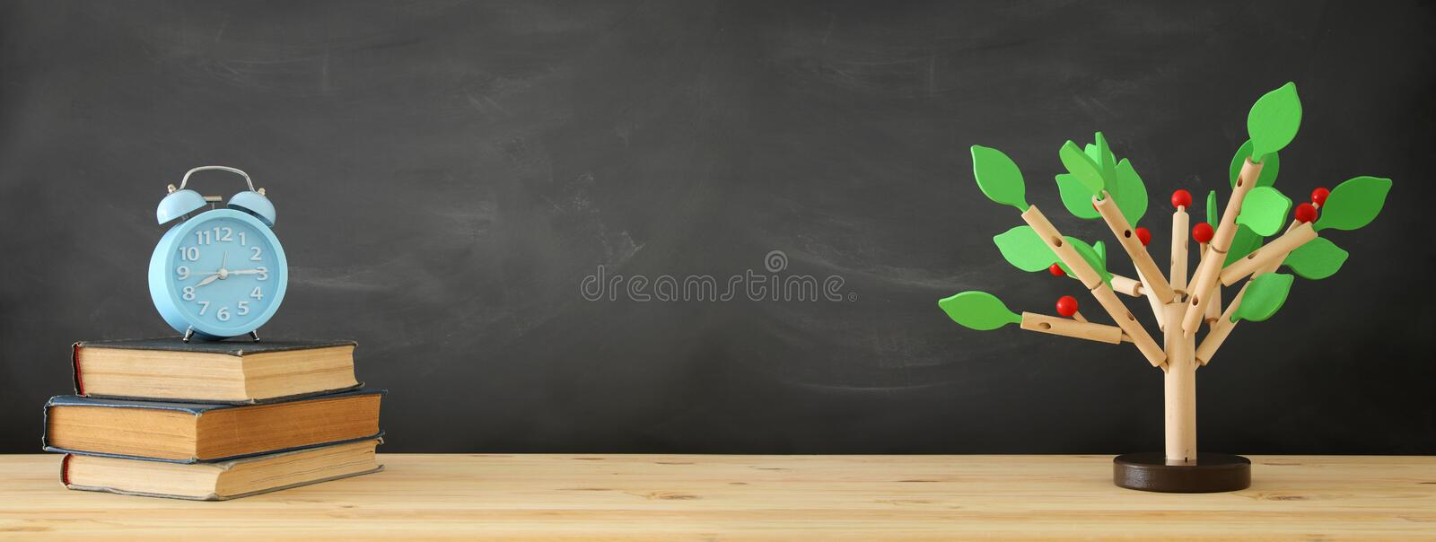 banner of open book and wooden tree puzzle over blackboard background. education and knowledge concept. royalty free stock photos