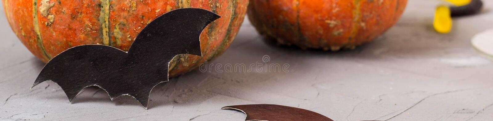 Banner of orange pumpkin and paper bats on white table, halloween concept stock images