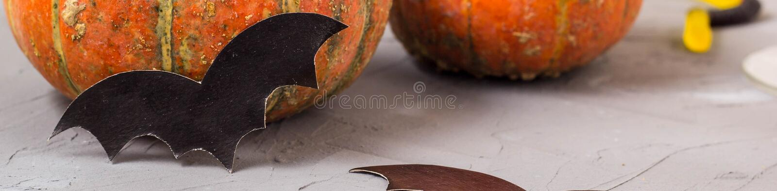 Banner of orange pumpkin and paper bats on white table, halloween concept. Holiday, spooky, autumn, decoration, background, symbol, scary, season, october stock image