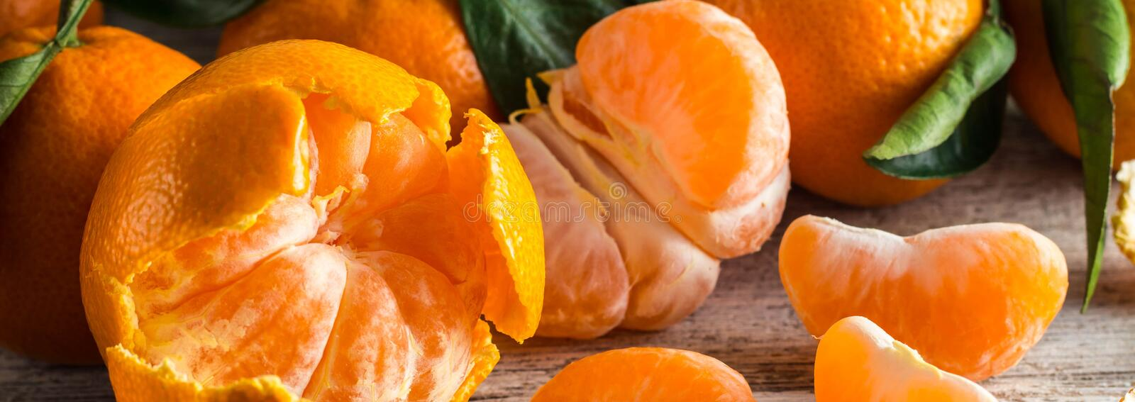 Banner of orange tangerines with green leaves on white wooden background. Peeled mandarin slices stock images