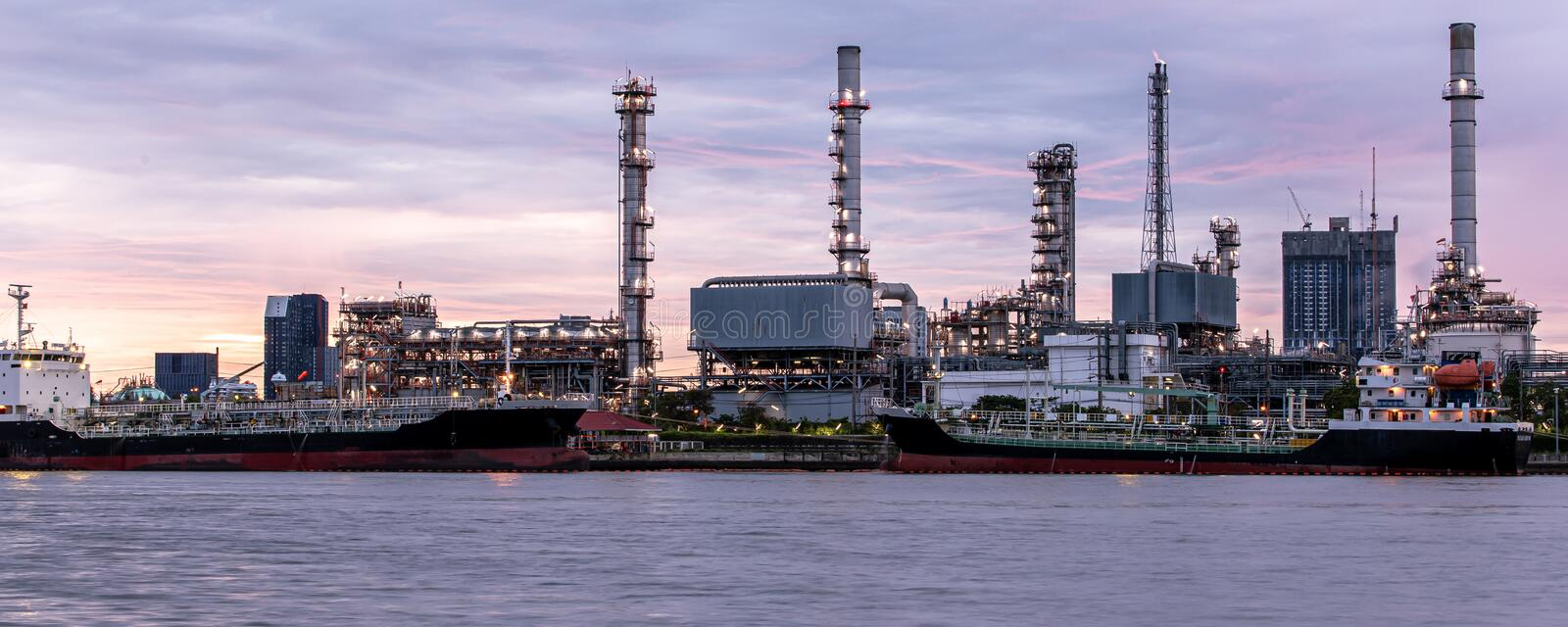 Banner of petroleum oil refinery plant beside river in twilight time. Crude Oil Process machinery stock images
