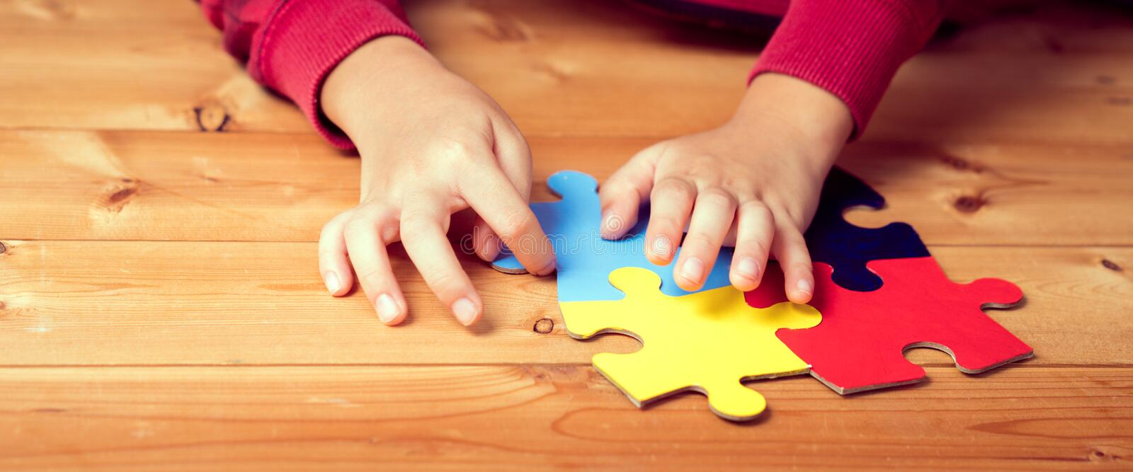 Banner picture of an autistic child`s hands playing a puzzle symbol of Public awareness for autism royalty free stock images