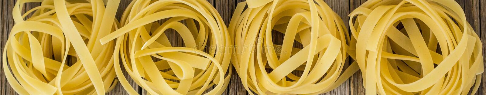 Banner of Nests of raw fettuccine pasta on the wood background. Banner of Raw fettuccine pasta on the wood backgroud ready for cooking. Top view. Copy space stock images